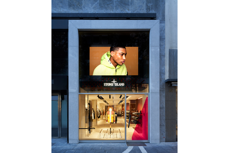 Exterior shot of Stone Island storefront with large photo of a model in a lime green hooded sweatshirt above the entrance