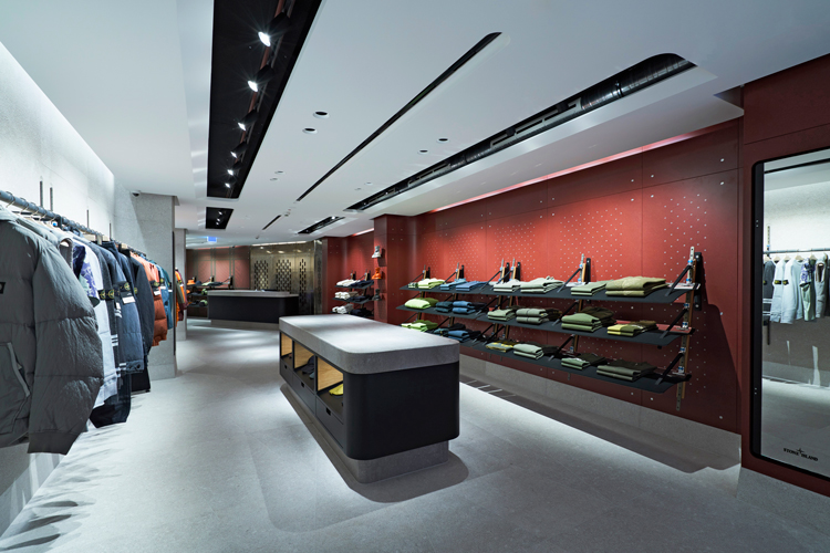 Stone Island store interior from the back of the store, with racks of jackets on the right and stacks of folded garments on the left