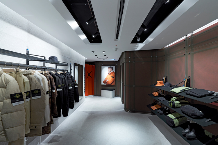 Stone Island store interior with racks of jackets on the left and stacks of folded garments on the right