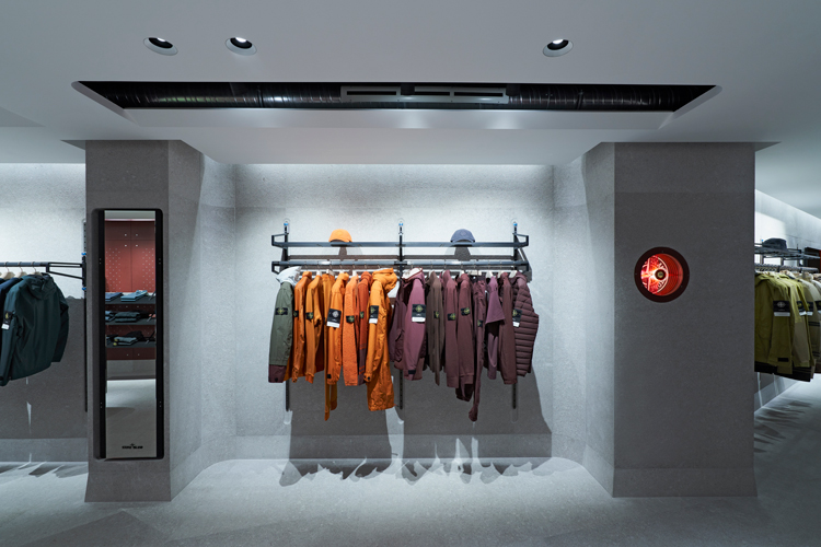Stone Island store interior with rack of jackets on the left and stacks of folded garments on the right, large photo of a model in an orange jacket in the back