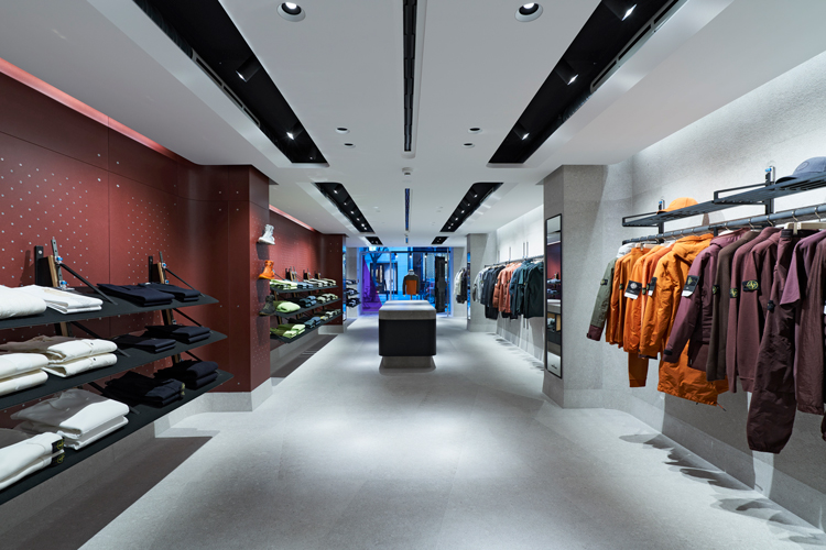 Stone Island store interior focusing on a rack of maroon, orange, and green jackets