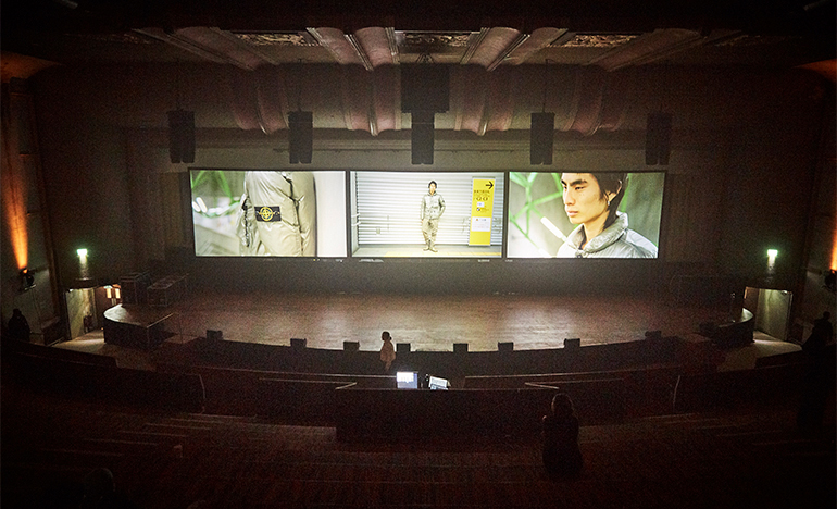 Inside a theatre with three screens on the stage showing different views of model in a Stone Island gray, lightweight jacket.