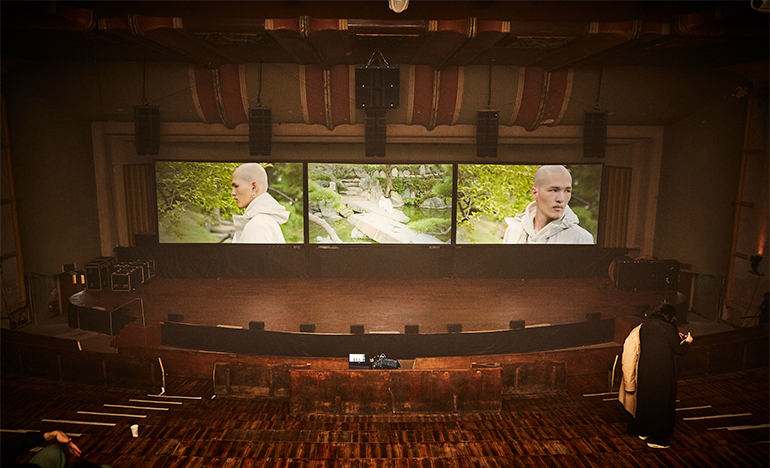 Inside a theatre with three screens on the stage showing different views of model in a Stone Island white hoodie.
