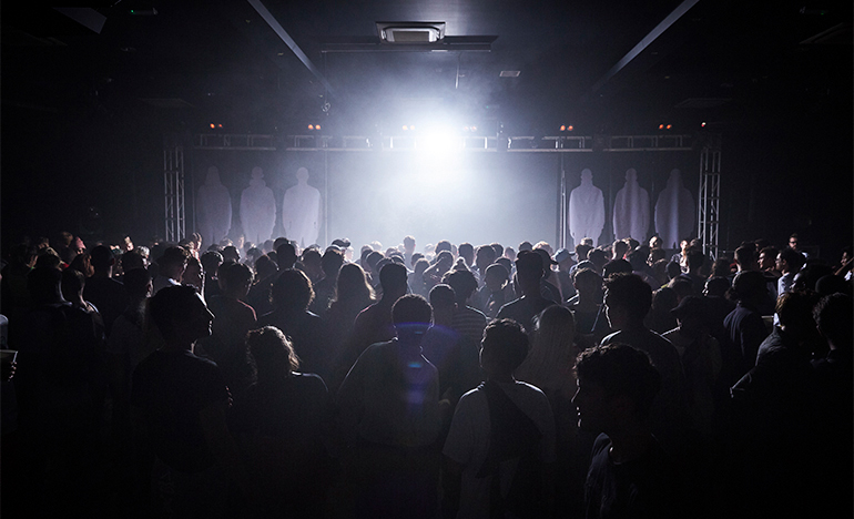 Club scene with people standing in front of black, full length, vertical banners with white silhouettes of guys in Stone Island jackets.