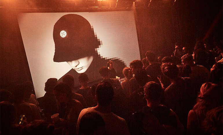 Large screen behind DJ showing model wearing a Stone Island hat.