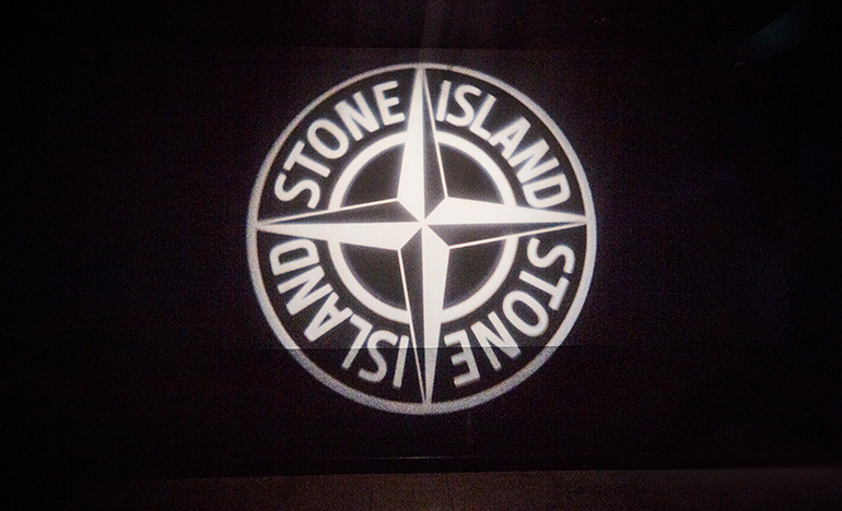 The Stone Island compass logo in neon lights.