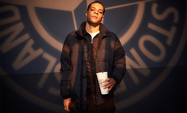 Man standing in front of the Stone Island compass logo, holding a paper cup with the same logo.