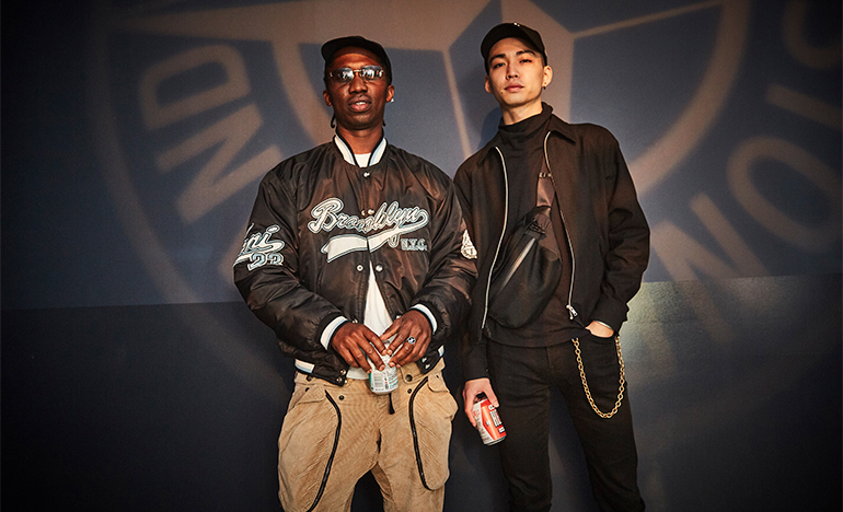 Two cool guys with beers, wearing black jackets and standing in front of the Stone Island compass logo.