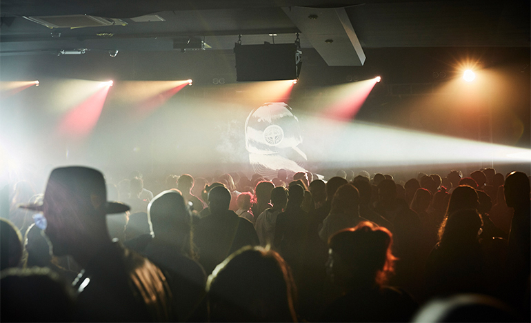 Club scene with laser lights with a Stone Island cap projected onto a screen and a silhouette of a guy wearing a trilby hat.