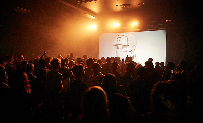 People watching a large screen in nightclub.