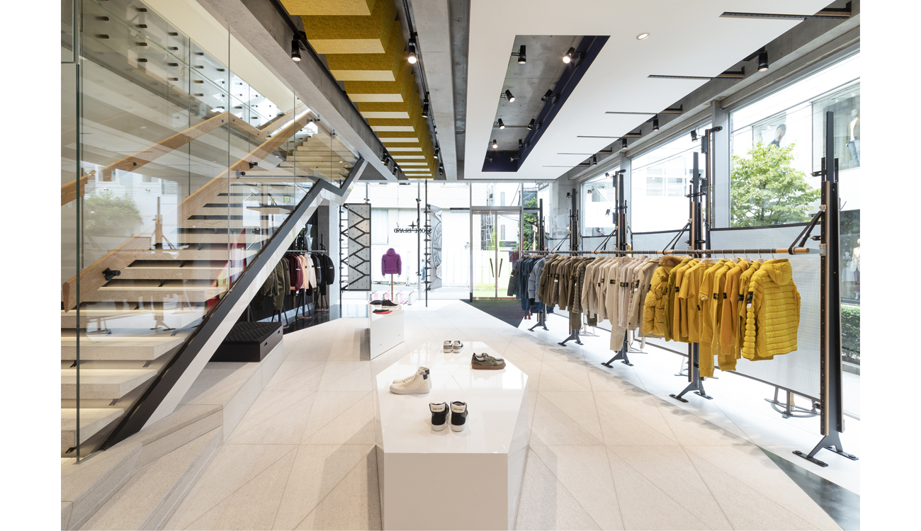 Store interior with staircase, jackets organized by color on clothes racks and shoes on white contemporary display tables.