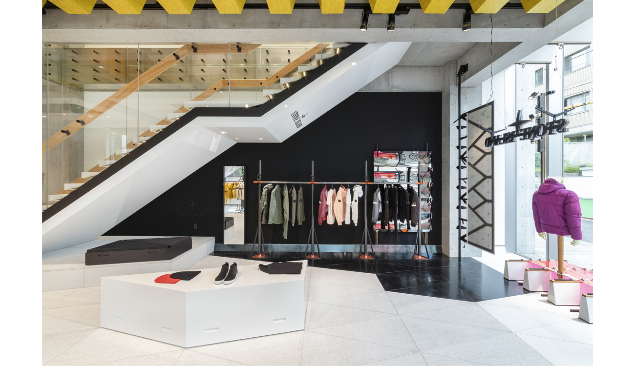 White, bright store interior with a rack of different colored clothes standing against a black wall.