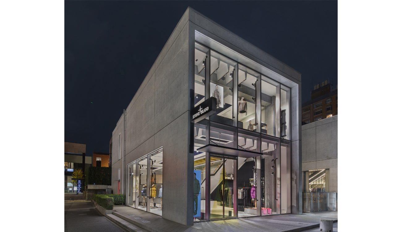 Street view of store set within a freestanding, glass and concrete building lit up at night.