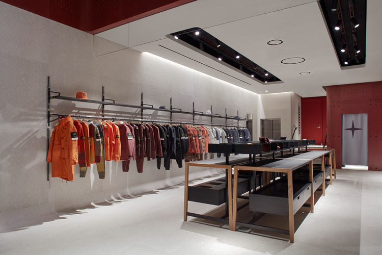 Interior view of the store facing the front with jackets arranged by color hanging on a rack on the right and display table in the center
