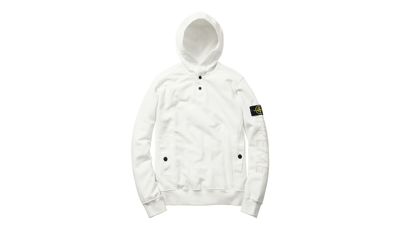 White sweatshirt with hood and diagonal pockets, with Stone Island badge and Supreme written on left arm.