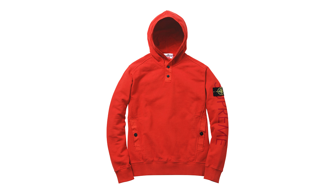 Red sweatshirt with hood and diagonal pockets, with Stone Island badge and Supreme written on left arm.