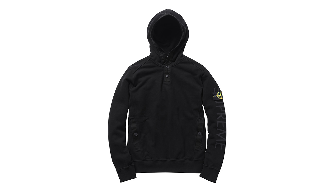 Black sweatshirt with hood and diagonal pockets, with Stone Island badge and Supreme written on left arm.