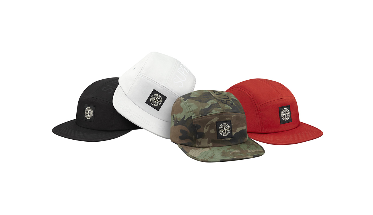 Four baseball caps in black, white, camouflage and red all with the Stone Island compass patch on the front.