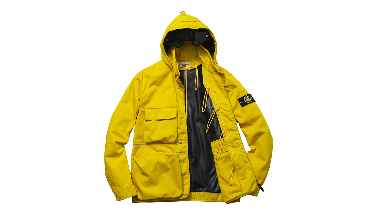 Yellow, hooded jacket with Stone Island logo badge on left arm, open to reveal black lining.