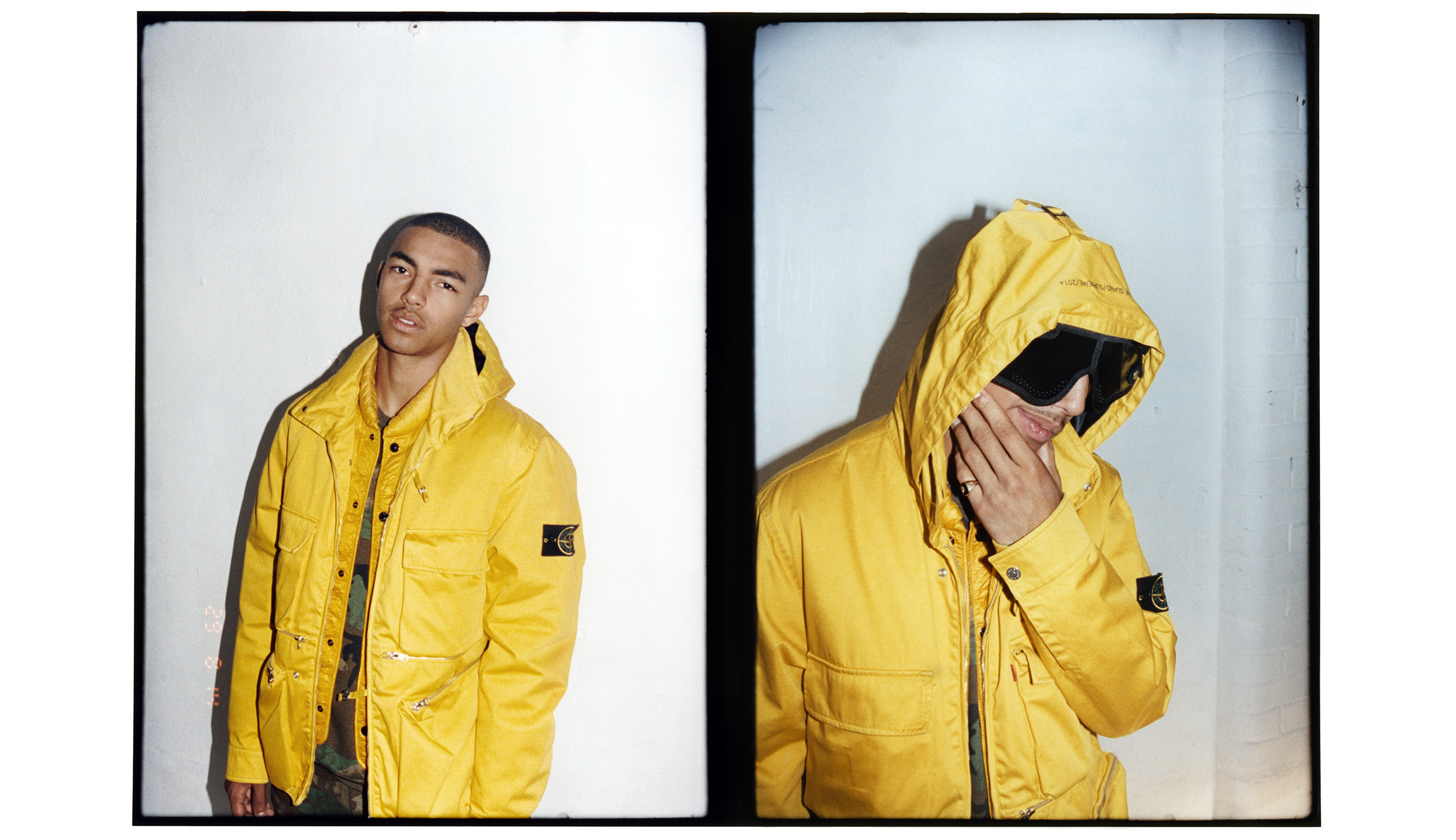Two models wearing different yellow jackets with Stone Island logo badge on left arm.