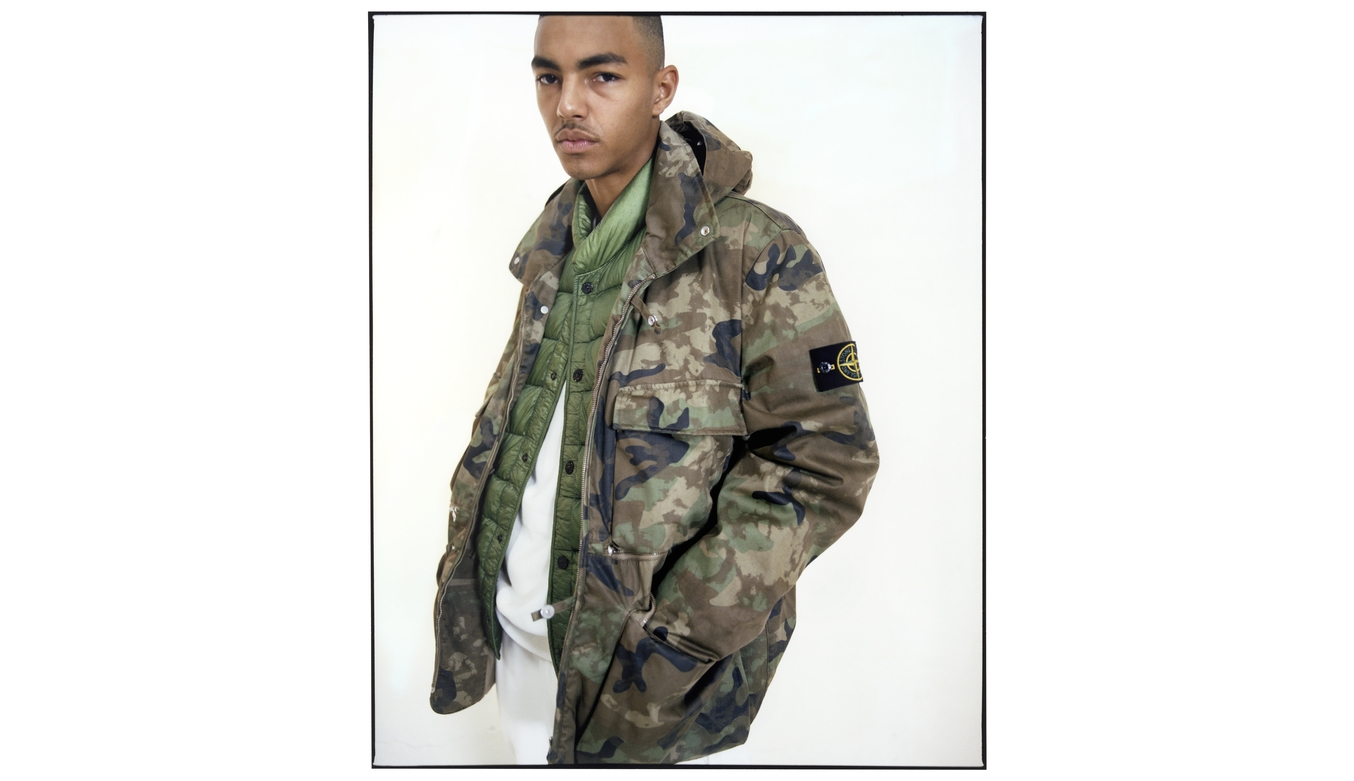 Model wearing camouflage jacket over green quilted jacket and white tracksuit.