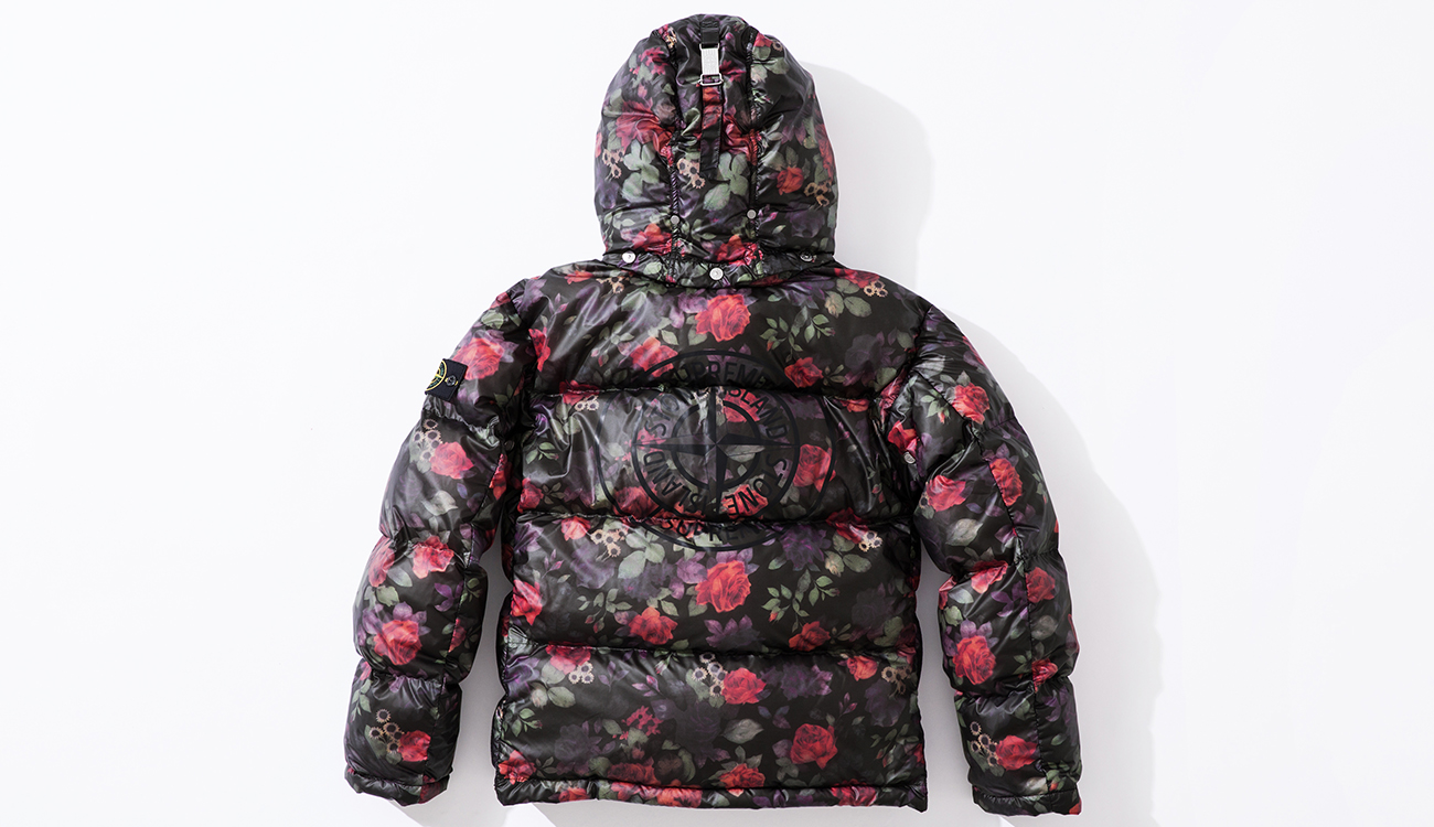 Back of down jacket in Lamy Cover fabric with black and floral print and the Stone Island Supreme compass logo on the back.