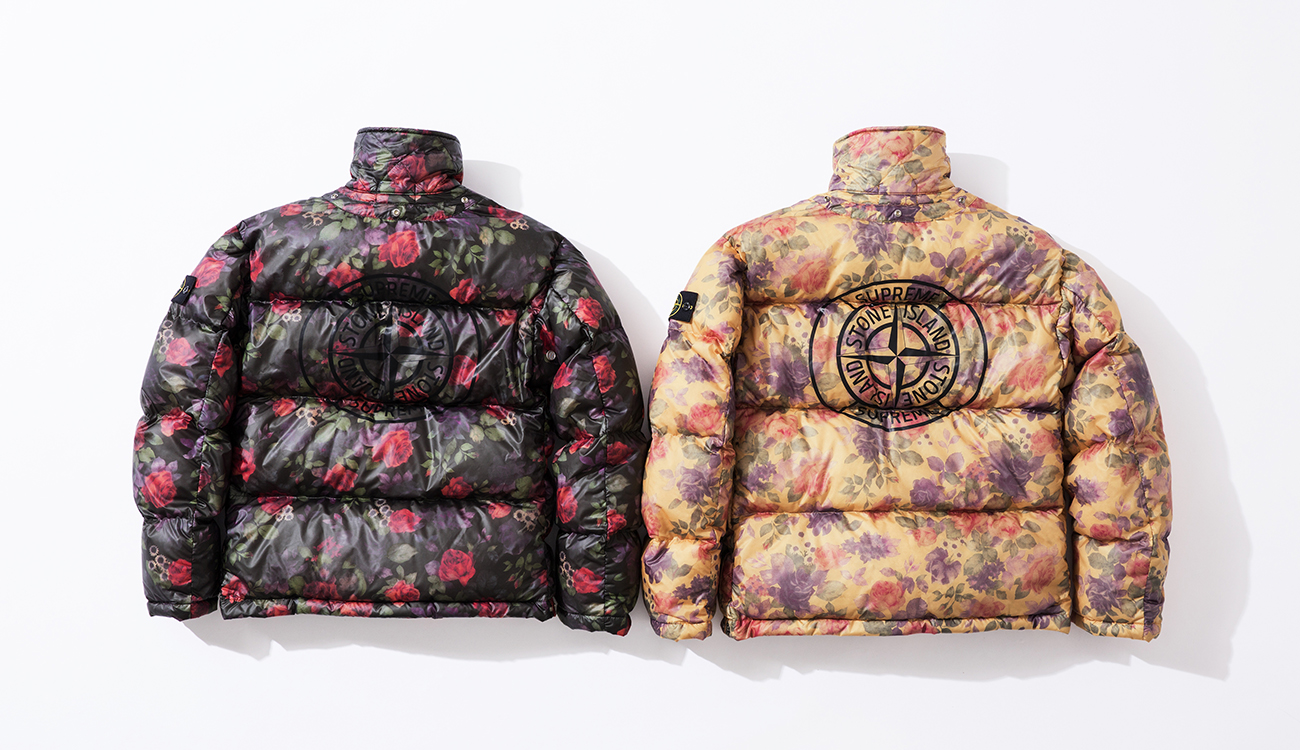 Back of two down jackets in Lamy Cover fabric, left one in black, right one in cream, both with floral print and the Stone Island Supreme compass logo on the back.