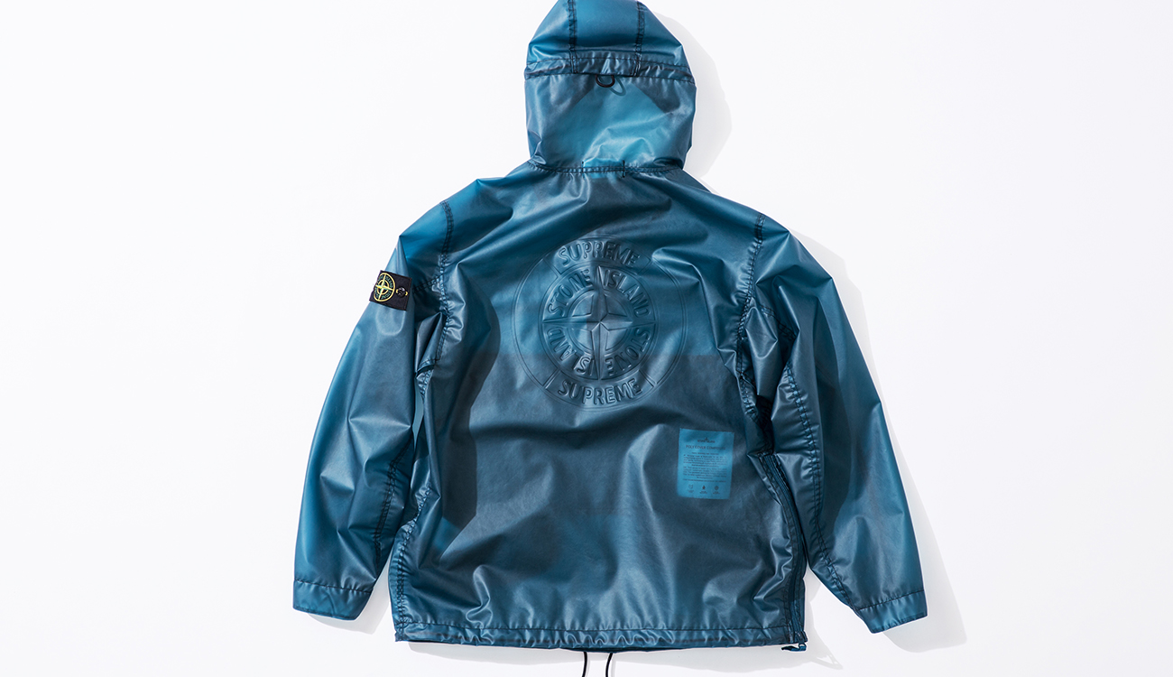 Back of blue anorak in Poly Cover Composite fabric with the Stone Island Supreme compass logo on the back.
