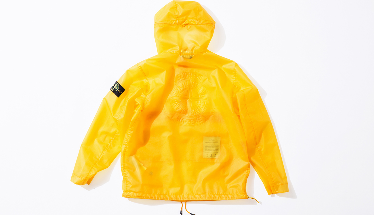 Back of yellow anorak in Poly Cover Composite fabric with the Stone Island Supreme compass logo on the back.