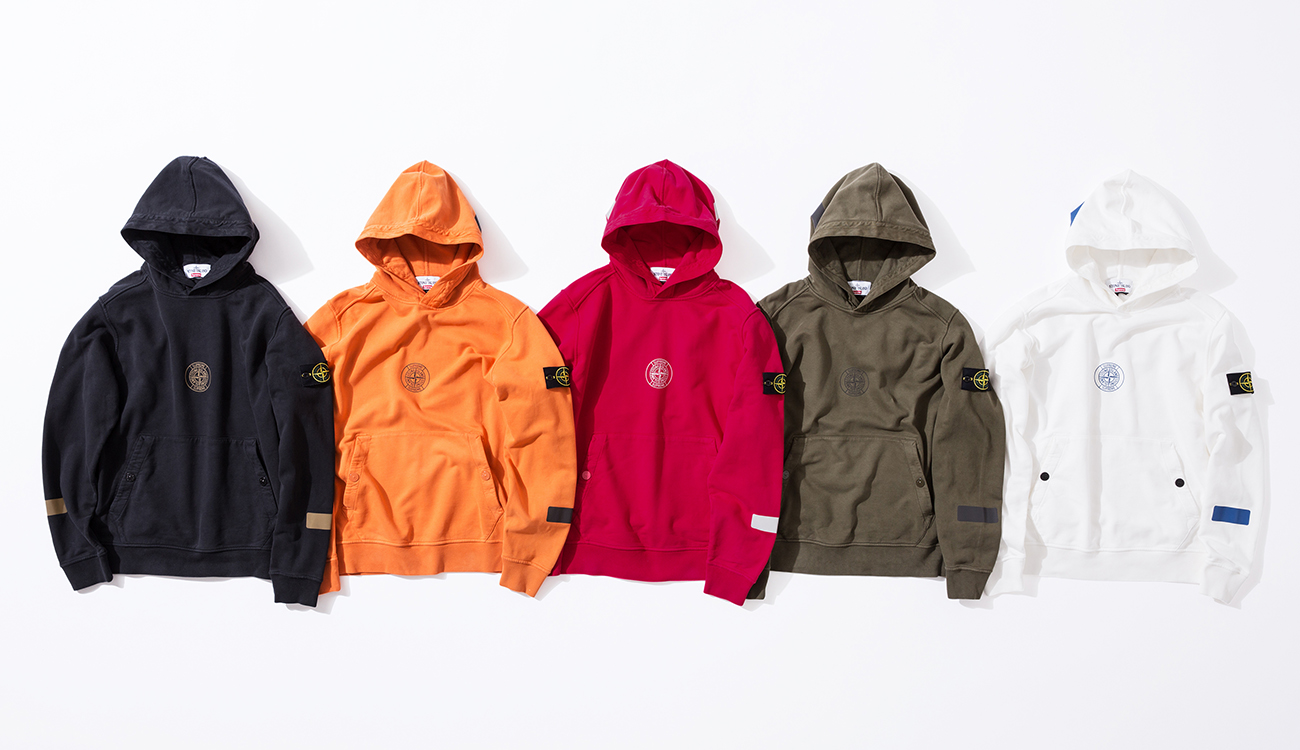 Front side of five hoodies in black, orange, red, green and white with the Stone Island Supreme compass logo in the center.