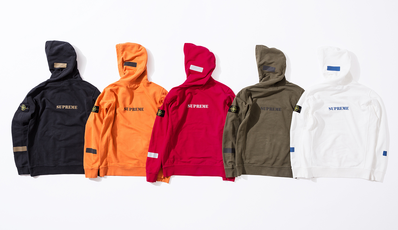 Back side of five hoodies in black, orange, red, green and white with Supreme logo on the back.