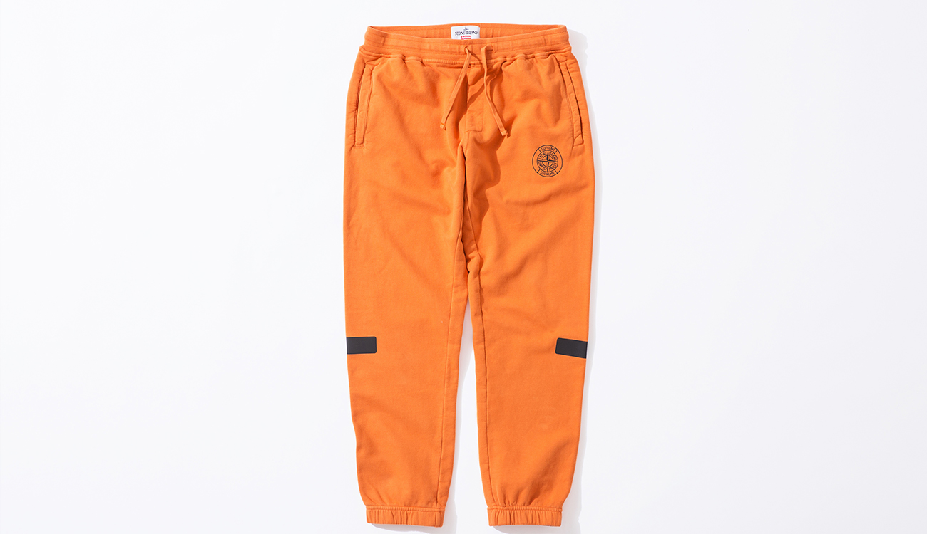 Front of orange tracksuit bottoms in cotton, fleece fabric, with the Stone Island Supreme compass logo on the right.