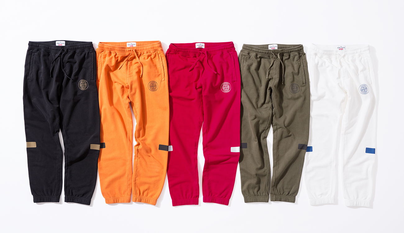 Front side of five tracksuit bottoms in cotton, fleece fabric with the Stone Island Supreme compass logo on the right, in black, orange, red, green and white.