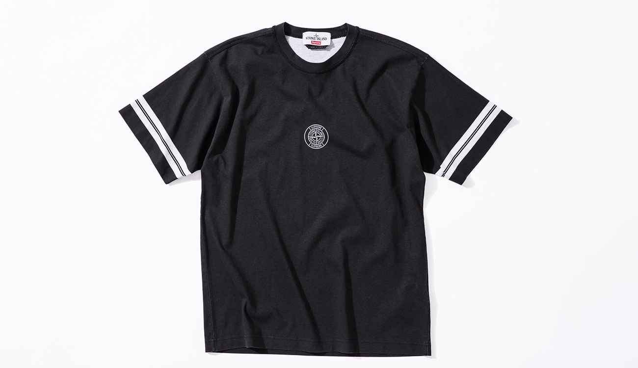 Black, short sleeve T shirt with white stripes on sleeve and the Stone Island Supreme compass logo in the center.
