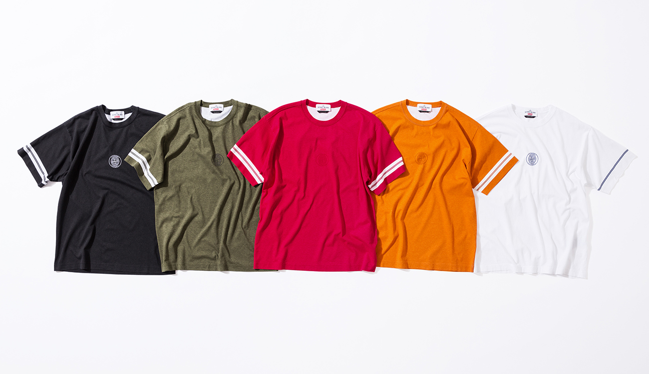 Five crew neck T shirts in black, green, red, orange and white all with white stripes on the sleeves and the Stone Island Supreme compass logo in the center.