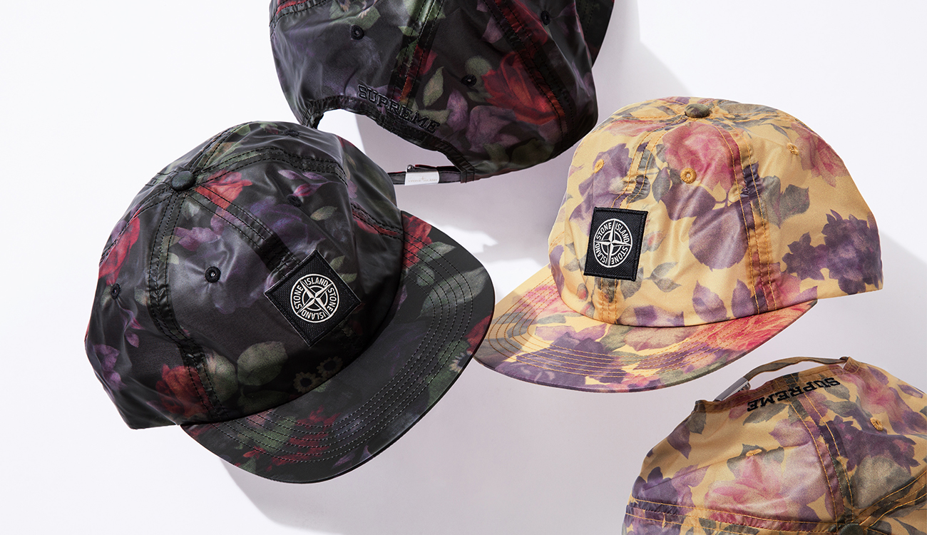 Different colored, floral print, baseball caps in black and cream with the Stone Island compass pach in the front and Supreme logo in the back.