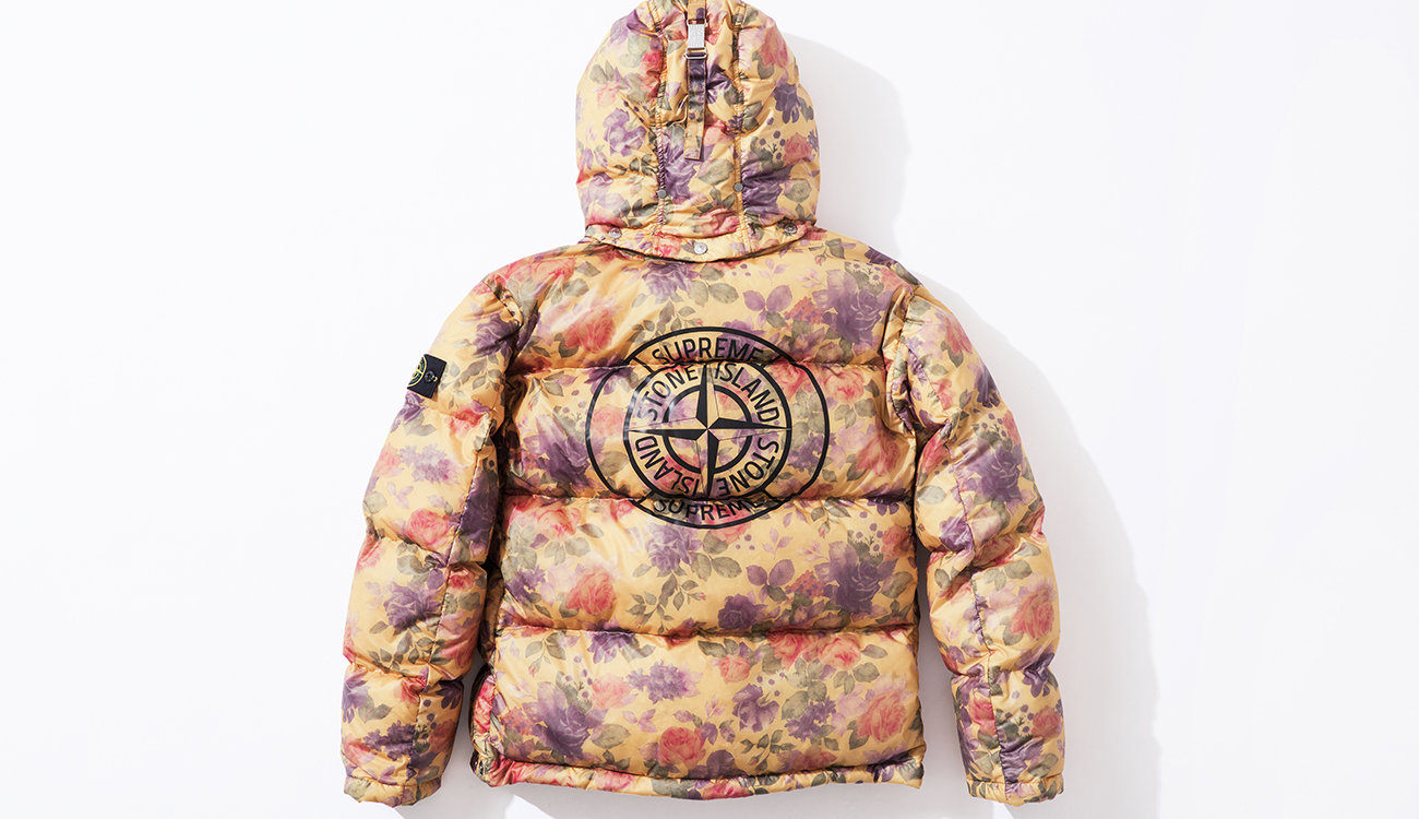 Back of down jacket in Lamy Cover fabric with cream and floral print and the Stone Island Supreme compass logo on the back.