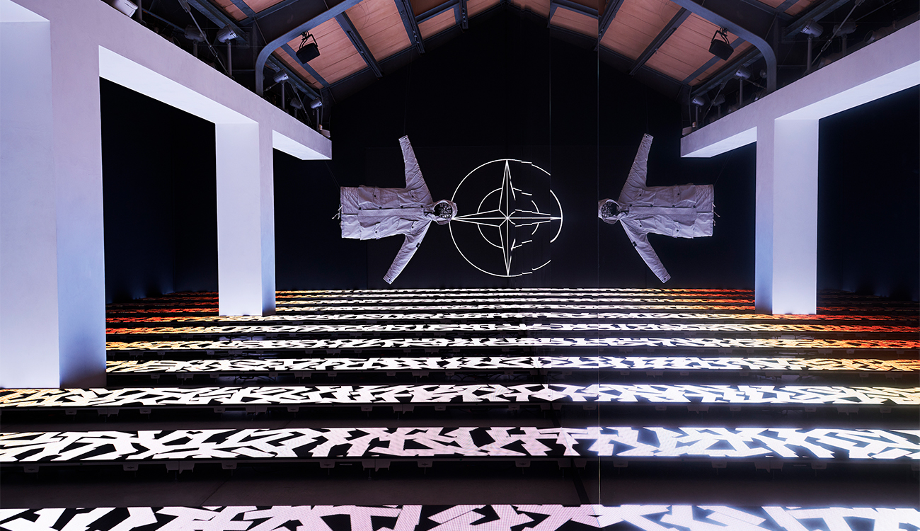 Artistic installation of two white Stone Island jackets suspended horizontally in space against the Stone Island compass logo.