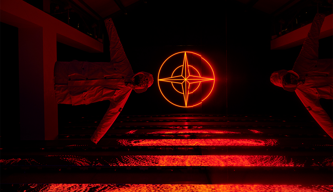 Artistic installation lit in red of two jackets suspended horizontally in space against the Stone Island compass logo.