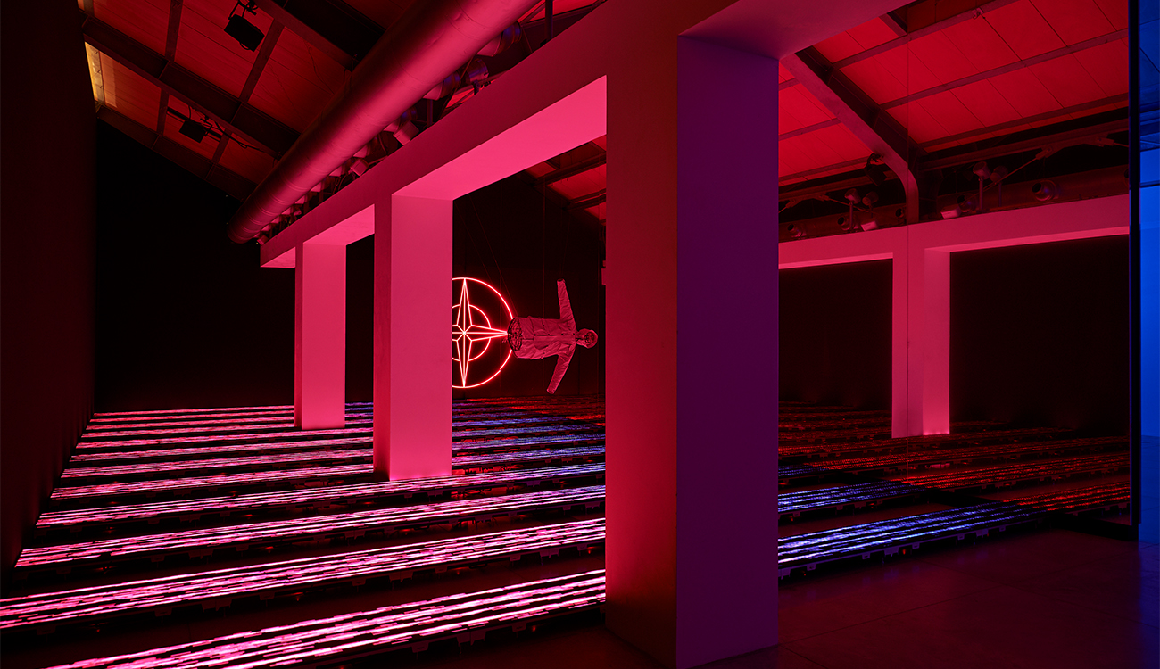 Artistic installation lit in pink of a jacket suspended horizontally in space against the Stone Island compass logo.