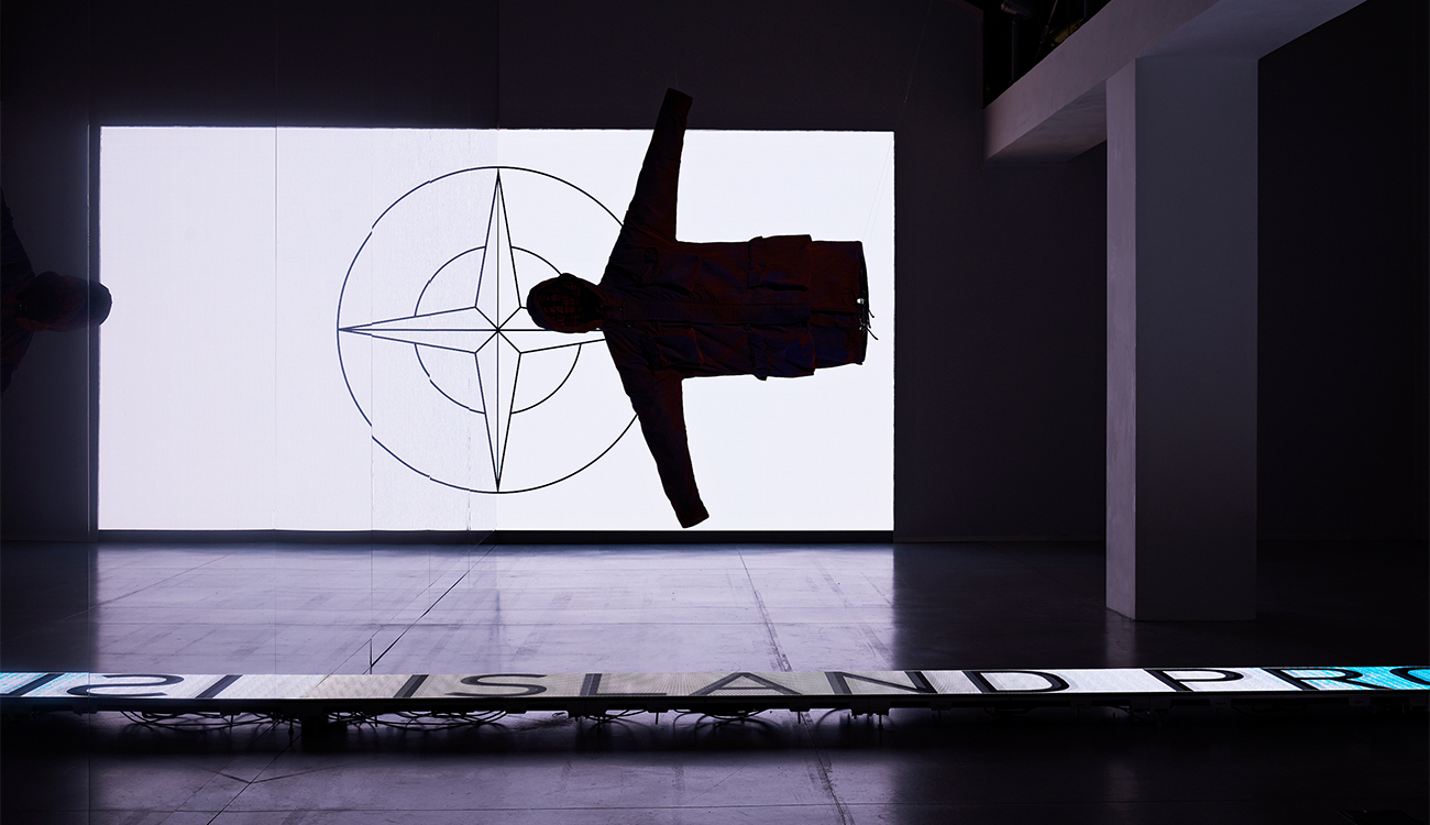 Artistic installation of a jacket suspended horizontally in space against the Stone Island compass logo lit up in black and white.