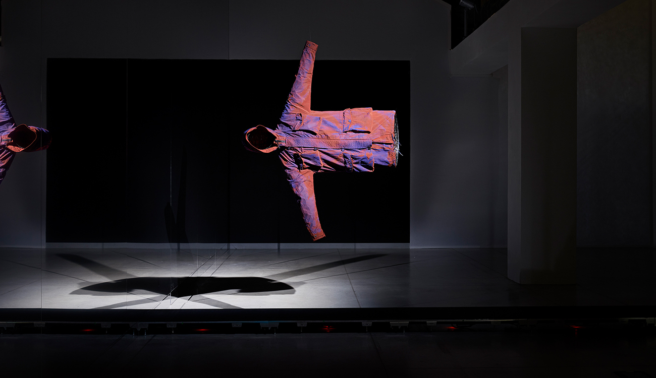 Artistic installation of a jacket suspended horizontally in space seen from the front.