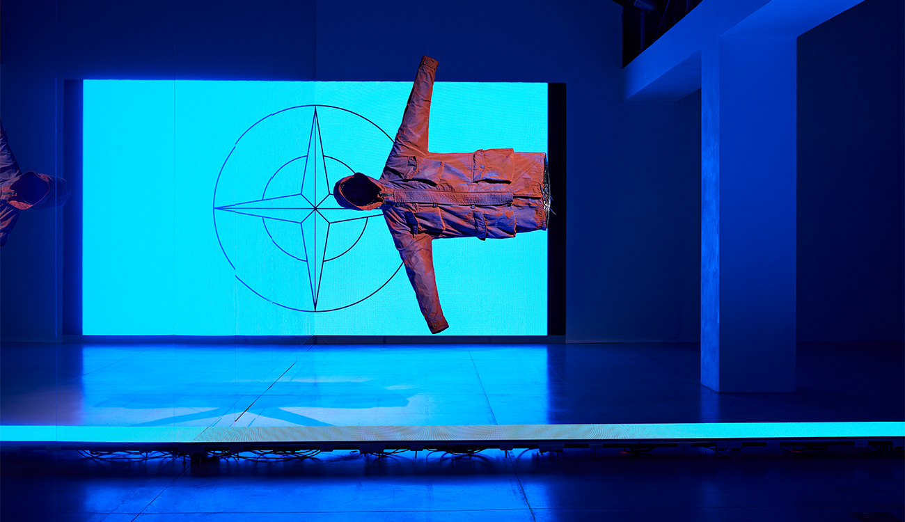 Artistic installation of a jacket suspended horizontally in space against the Stone Island compass logo lit up in blue.