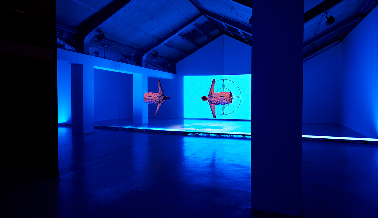 Long view of artistic installation of two jackets suspended horizontally in space and the Stone Island compass logo lit up in blue.