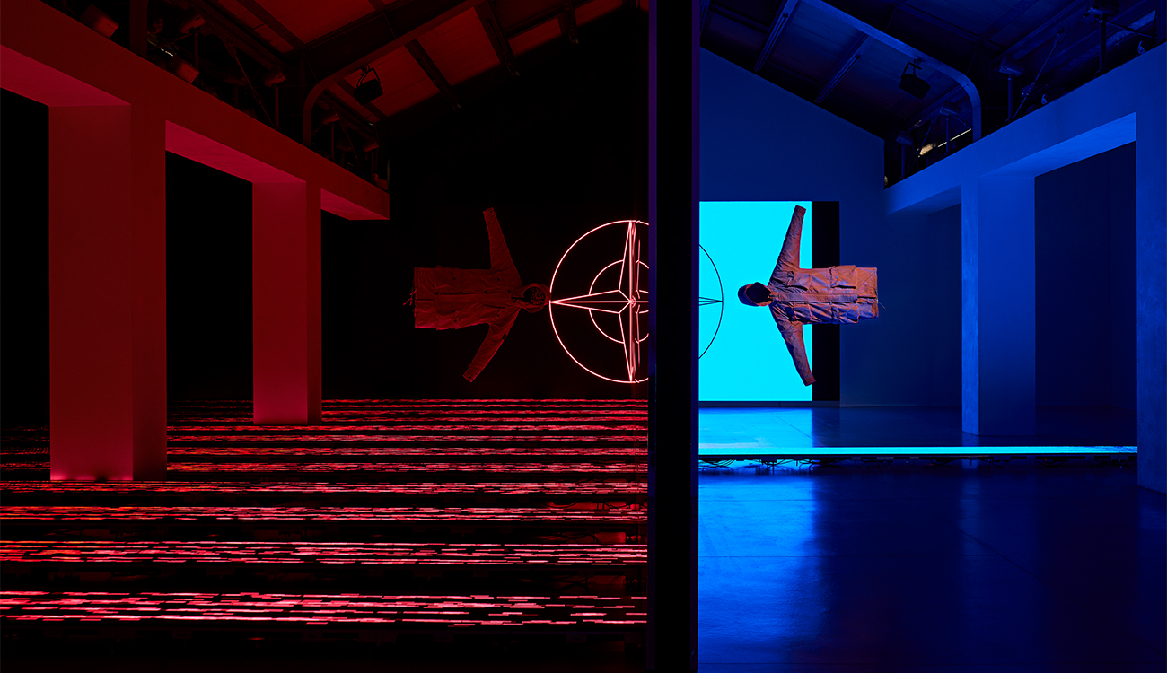 Artistic installation lit in blue and red of two jackets suspended horizontally in space against the Stone Island compass logo.