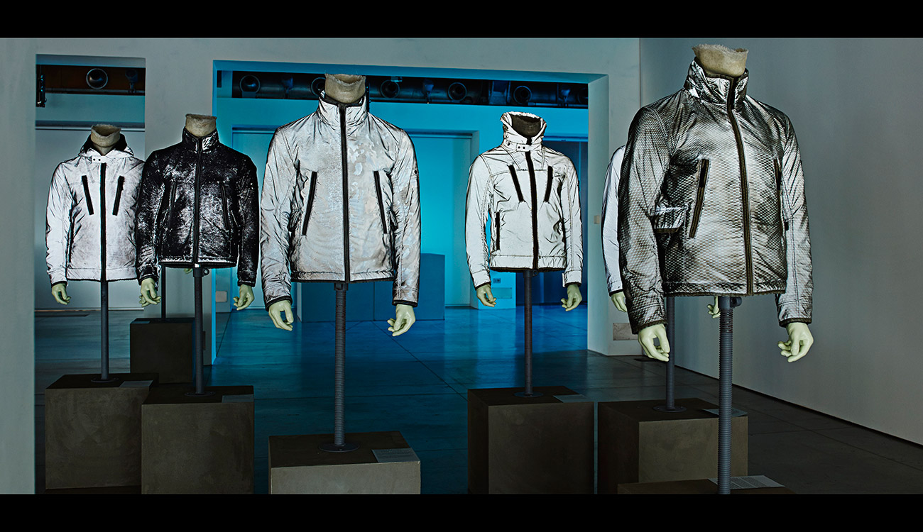 6 mannequins wearing jackets in different shades of gray, black and white.