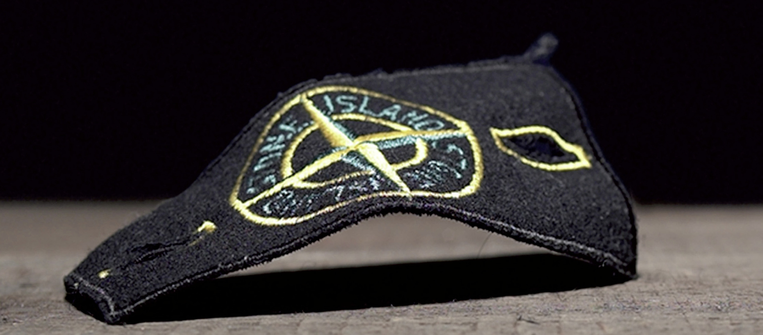 Close up of the Stone Island detachable badge in black felt with the compass rose embroidered in gold and green.