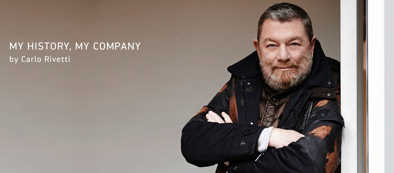 CEO of Stone Island Carlo Rivetti leaning on a doorway with his arms folded across the chest.