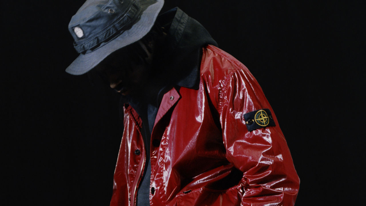 Model wearing a red jacket in New Silk Light fabric and a blue boonie hat.