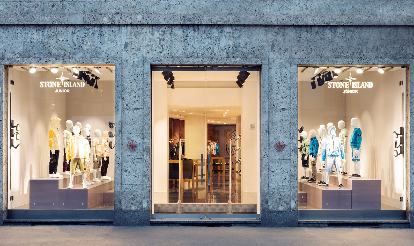 Street view of storefront showing two full length windows, a central glass entrance and brightly lit store interior.